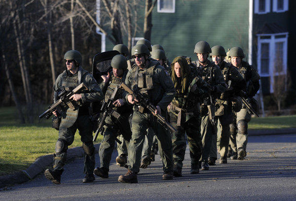 A Connecticut state police tactical unit marches away from 36 Yogananda Street (not visible in photograph), the home that shooter Adam Lanza lived in with his mother Nancy. Adam shot and killed her while she slept in bed before heading to Sandy Hook Elementary School Friday morning.