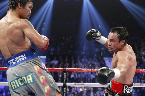 Manny Pacquiao (L) of the Philippines watches as Juan Manuel Marquez of Mexico is knocked down in the fifth round of their welterweight fight at the MGM Grand Garden Arena in Las Vegas.