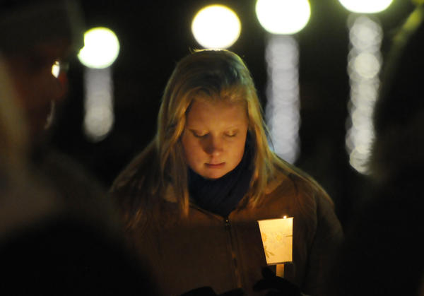 Corinne McLaughlin, a student at the University of Hartford studying teaching, bows her head during a candlelight vigil at Hartford's Bushnell Park Friday night in memory and prayer for the students and teachers who died at Sandy Hook Elementary School in Newtown earlier in the day.