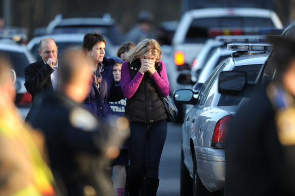 Parents grieved in the parking lot at Sandy Hook Elementary School Friday after a gunman killed 20 children. A total of 28 persons were killed.