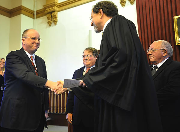 Michael D. Lorensen, left, is sworn in Friday by Chief Judge David H. Sanders. Judges John Yoder and Andrew Frye look on.