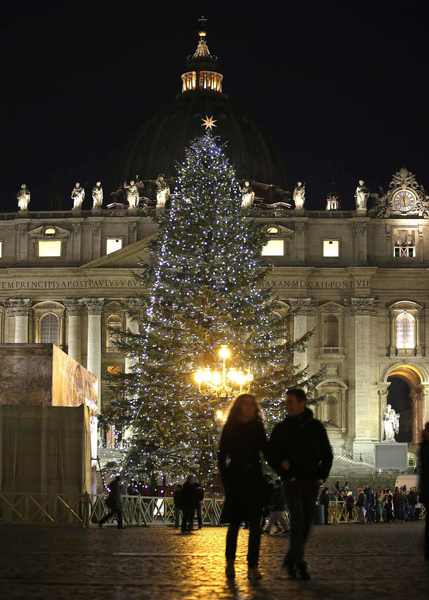 The Vatican Christmas tree is lit up after a ceremony as a couple walk in Saint Peter's Square at the Vatican December 14, 2012.