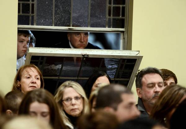 Mourners look in through the window of St. Rose of Lima Roman Catholic Church at a vigil service for the shooting victims.