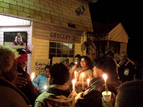 Tara Bozick/Daily Press photo Friends and family pray, cry and share memories of Everette Harrison, 48, of Hampton at the site he was shot and killed in front of White's Grocery Store #2 at 19th and Buxton Avenue.