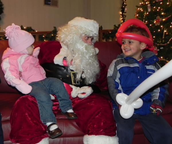 Sarah Weaver, 18 months, sits on Santa's lap while Micah Weaver, 4, shares a smile with Jolly Old St. Nick on Friday at the 22nd annual Greencastle-Antrim Heritage Christmas.