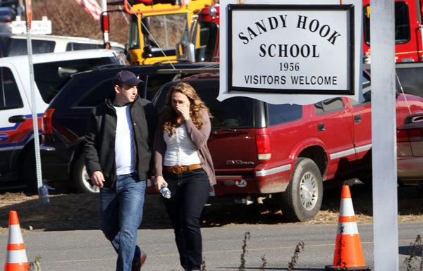Parents walk away from Sandy Hook Elementary, the scene of a deadly massacre, on Friday.