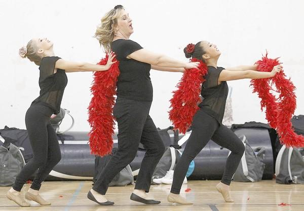 "Corona del Mar High School teacher Tammy Owney, center, practices with teammates Bailey Ashton, 18, left, and Taylor Chen, 14, right, before the ""Dancing with the Teachers"" competition Thursday."