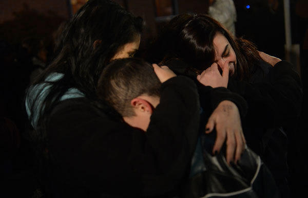 People gather at a prayer vigil at St. Rose Church in Newtown, Conn., on Friday.