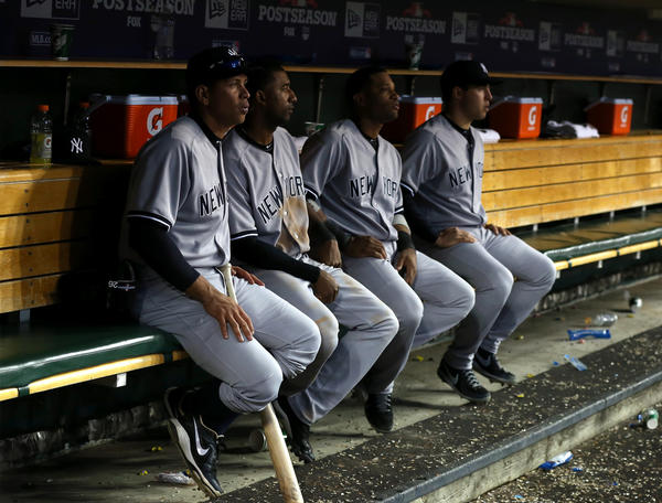 (L-R) Alex Rodriguez #13, Eduardo Nunez #26, Robinson Cano #24 and Mark Teixeira #25 of the New York Yankees look on from the dugout late in the game against the Detroit Tigers during game four of the American League Championship Series.