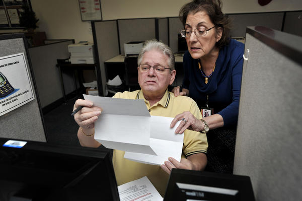 Mike Wight, who worked at the Sparrows Point steel mill for 47 years, shows Varvara Kymbriti paperwork as he enrolls in the Maryland Workforce Exchange program at the steelworker assistance center at Eastpoint.