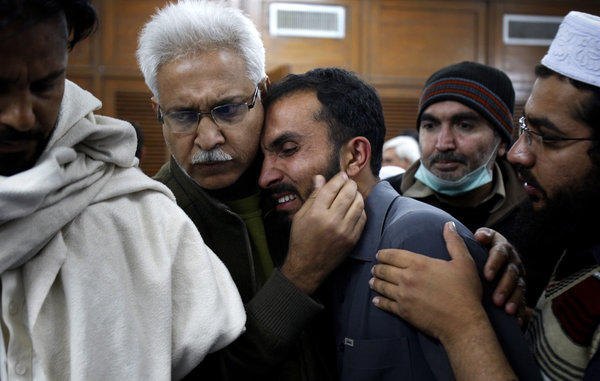 A Pakistani at a hospital in Peshawar comforts another man mourning a relative killed Saturday during a rocket attack by militants on a nearby airport.