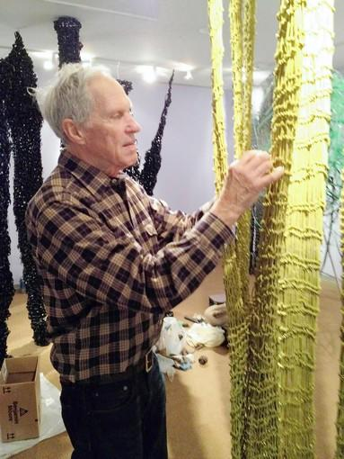 Ted Hallman works on 'Suspended Harmonies,' a fiber art installation at the MIchener Art Museum intended to express the artist's vision of Bucks County landscape tradition. The show is on display through March 3.