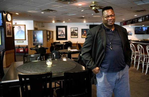 Larry Holmes poses in his new restaurant, Champs Corner in Easton.