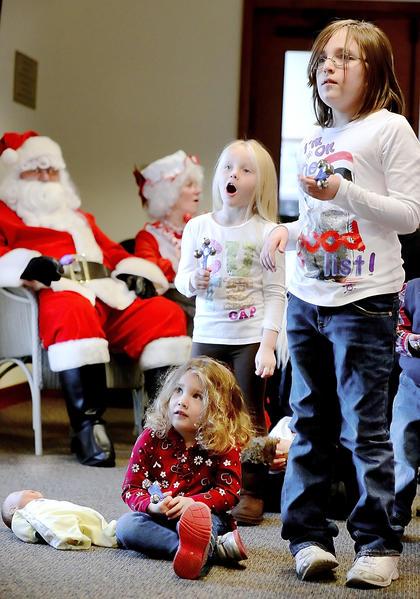 "Elena Meekins, sitting, Lily Kane and Chloe Keller sing ""Jingle Bells"" at Breakfast with Santa held Saturday at the Smithsburg Library."