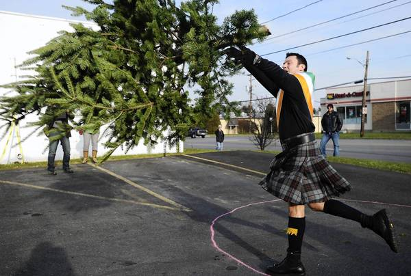Bethlehem Police Chief Jason D. Schiffer, tosses a Christmas tree during the 11th Annual Christmas Tree Toss for Charity Saturday afternoon at Jack Williams Tire and Auto Center.