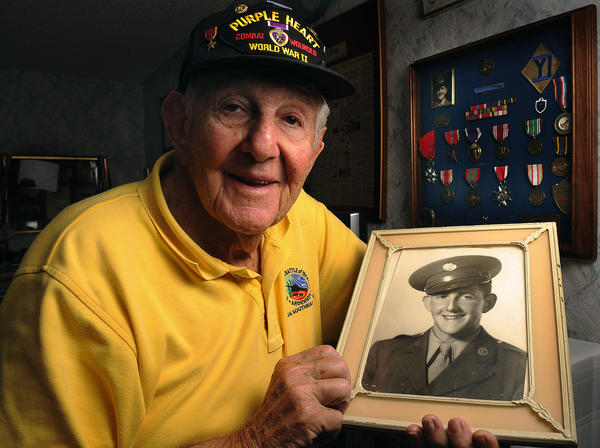George Fisher, 87,of Palm Beach, a WWII veteran of the Battle of the Bulge. He is holding a photo of himself as a 19-year-old Private First Class.