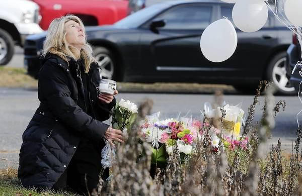 Andrea Jaeger places flowers and a candle at a makeshift memorial outside a firehouse in Newtown that was used as a staging area for families after the shooting at Sandy Hook Elementary School.