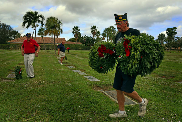 Greg Hardy, 63 an Army Airborne veteran carries wreaths at Memorial Cemetery in Deerfield Beach to place on the graves of veterans. He was working along with other members of the American Legion Post 162 in Deerfield Beach to honor the veterans.