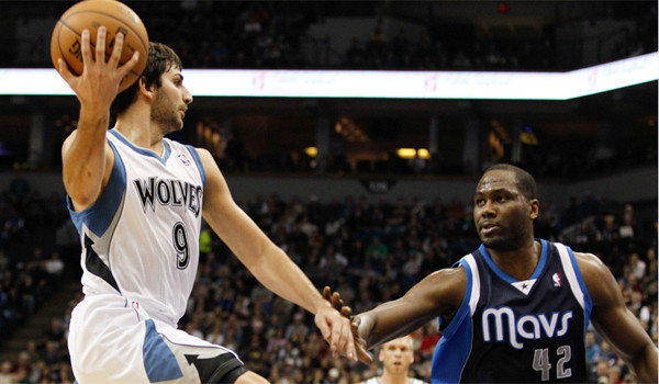 Minnesota's Ricky Rubio tries to pass the ball around Dallas' Elton Brand.
