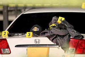 A gun, a hat and other items sit on a car in a Fashion Island parking lot near Macy's on Saturday. A gunman fired more than 50 rounds at the busy Newport Beach shopping mall. A suspect was arrested.