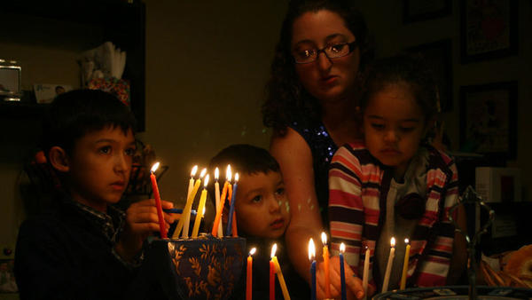 Xavier Campos, 6, lights the hanukiah with his brother Adrian, 4, as his mother Stephanie Campos and Natalia San Pedro, 3, prepare a separate hanukiah during Temple Beth Jacob's celebration of Hanukkah, Saturday evening.