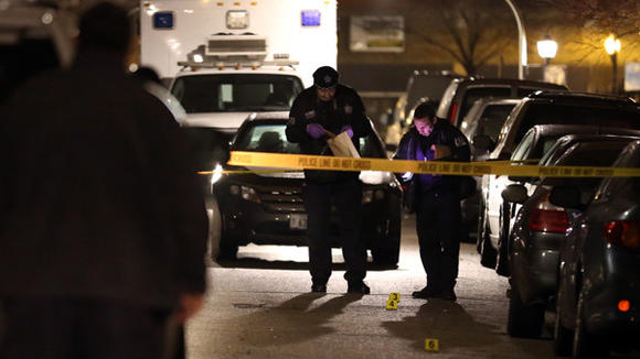 Police officers mark evidence in the 2400 block of West Flournoy Street after the fatal shooting of a 28-year-old man.