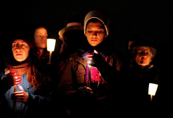 People shield their candles from the wind and light rain during a candlelight vigil in remembrance of the Newton, Conn. shooting victims at Green Lake Park in Seattle.