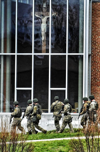 A SWAT team walks past a statue of the crucified Christ at Saint Rose of Lima school while responding to a called bomb scare that evacuated the church.