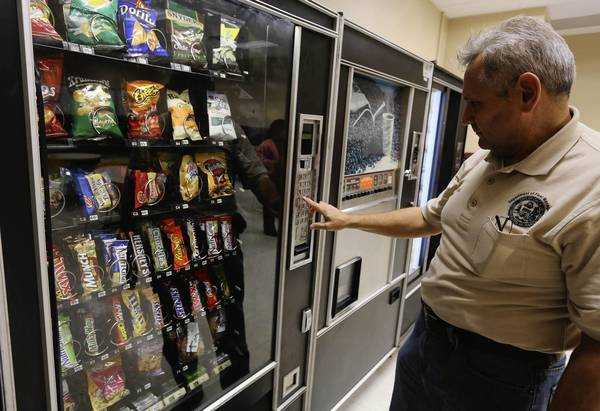 Natividad Garcia makes a selection from a vending machine at the city's Department of Fleet and Facility this month. A ordinance, backed by Mayor Rahm Emanuel, takes effect next month that will enforce strict rules on vending machines in city owned and leased buildings.