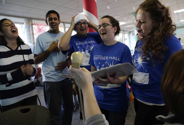 "University of Illinois at Urbana-Champaign students Katy Pippins, from left, Warren D'Souza, Jose Cuevas, Clare Curtin and Kasia Stelmach sing ""Feliz Navidad"" for Dial-a-Carol."