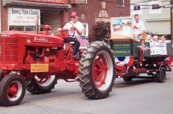 Ray Miller pilots his 1941 Farmall M during a parade with his grandchildren riding behind in a 1902 bobsled.