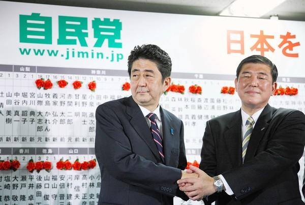 Shinzo Abe, left, the president of Japan's Liberal Democratic Party, shakes hands with the party's secretary-general, Shigeru Ishiba, at party headquarters in Tokyo. Behind them, red paper roses alongside candidates' names indicate election wins.