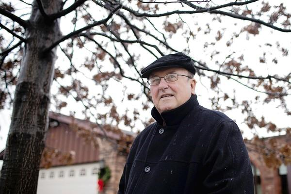 Frank Reid of Addison stands outside his home under a Penn Oak tree he planted for his wife, Betty, in the early 90s.