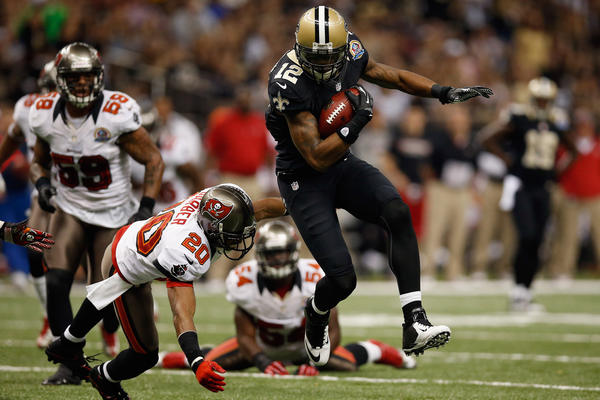 Marques Colston #12 of the New Orleans Saints is tackled by Ronde Barber #20 of the Tampa Bay Buccaneers at the Mercedes-Benz Superdome on December 16, 2012 in New Orleans, Louisiana. New Orleans won 41–0.