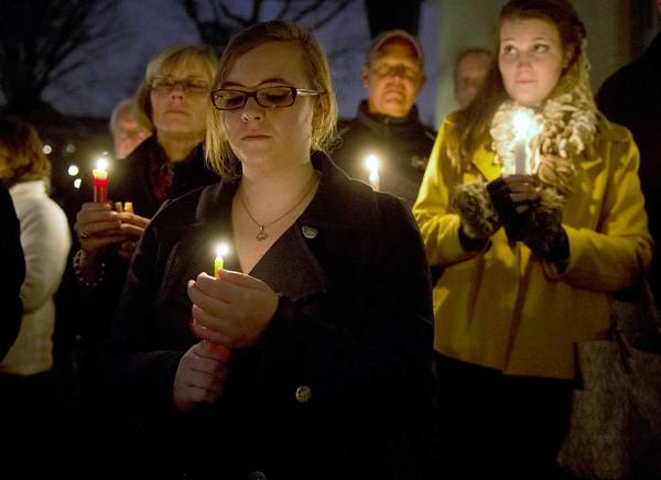 Molly Kennedy (front), 16, of Bethlehem, holds a candle at Central Moravian Church in Bethlehem during Sunday night's vigil for shooting victims and their families in Newtown, Conn.