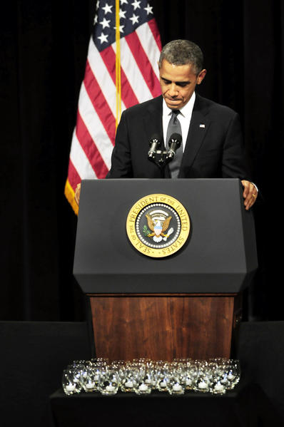 President Barack Obama makes an emotional address during a vigil in the Newtown High School auditorium. In front of the President are candles representing those who died during Friday's attack at the Sandy Hook Elementary School. Hundreds of local residents, including grieving families and first responders, filled the hall Sunday night.