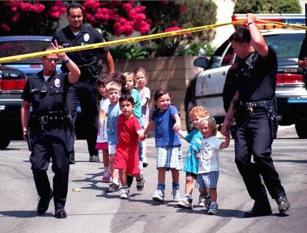 Children from the Jewish Community Center in Granada Hills are escorted to safer ground by LAPD officers after a gunman open fire at the center on Aug. 10, 1999. Three children and two adults were wounded