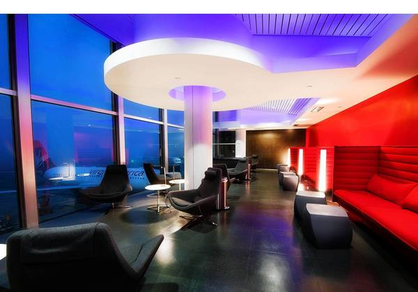 The Virgin America Loft at Los Angeles International Airport includes upholstered, wheel-shaped seats and flat-screen TVs. In addition to high-end snacks, the lounge offers aviation-themed drinks.