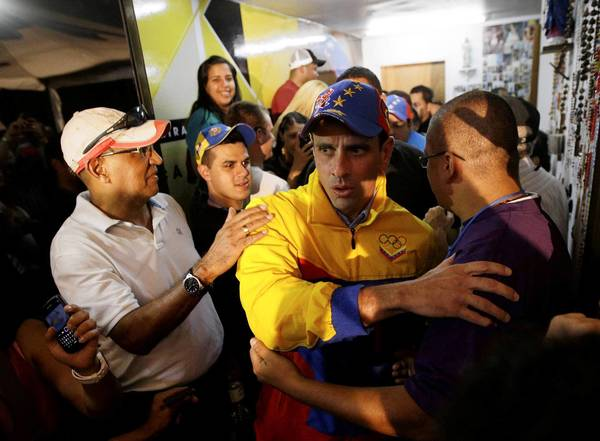Henrique Capriles, center, receives congratulations in Caracas as initial results show him winning reelection as governor of Venezuela's Miranda state.