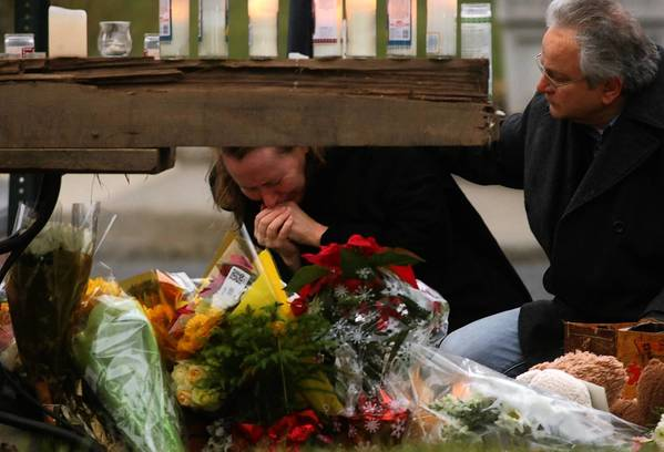 A couple grieves at a memorial for those killed in the shooting at Sandy Hook Elementary School in Newtown, Conn.