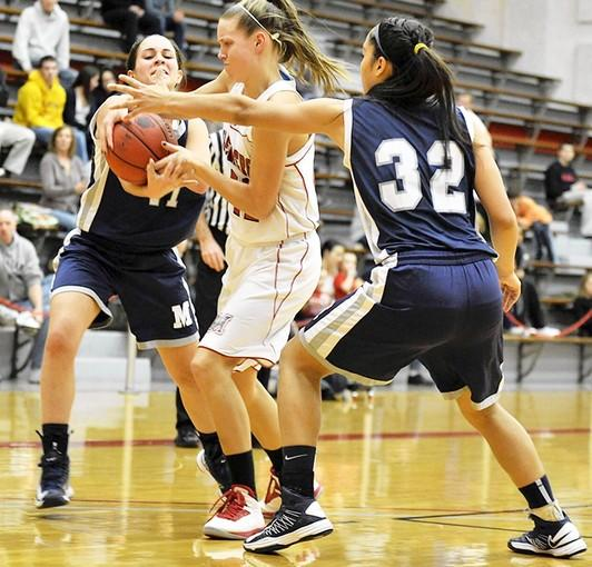 Moravian's Katie O'Rourke (left) and Alexis Wright fight to keep the ball away from Muhlenberg's Erin Laney.