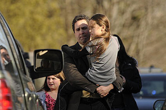 An unidentified family leaves the scene of the Newtown, Conn. school shooting on Friday. The first funerals for those slain will be on Monday.