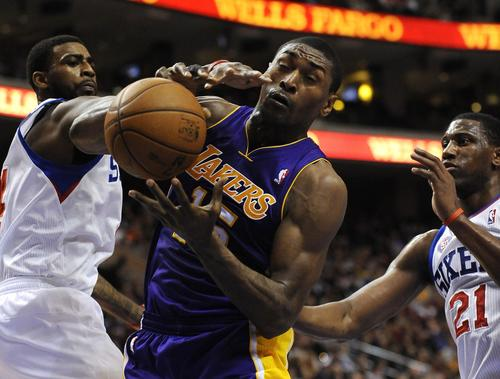 Metta World Peace pulls in a rebound against the Philadelphia 76ers' Dorrell Wright and Thaddeus Young.