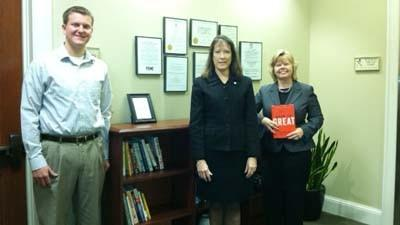 The Bank of Northern Michigan employee and Leadership Little Traverse graduate Garrett Urman (from left), Leadership Little Traverse chairwoman Anne McDevitt and bank senior vice president Kathy Erber stand in the leadership lending library area at the bank's Petoskey office.