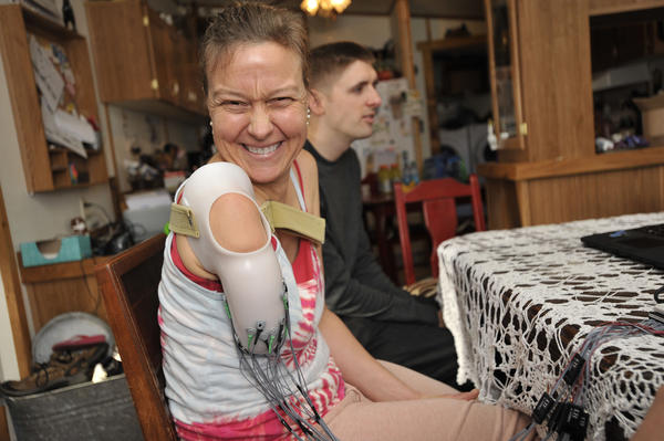 Dana Burke, a Pennsylvania woman who was shot in the arm 14 years ago, smiles before beginning another day of testing of a thought-controlled prosthetic arm. Mike Powell, a graduate student at Johns Hopkins is sitting next to her.