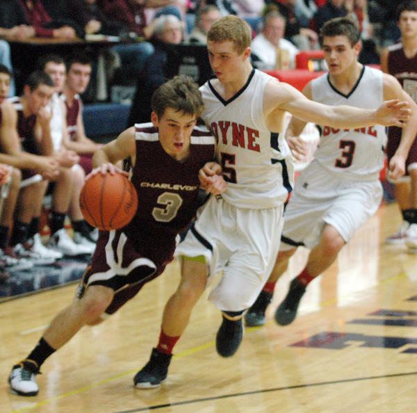 Charlevoix senior guard Charlie Hamilton (left) starts to drive on Boyne City sophomore Maceo Vroman during Friday's Lake Michigan Conference contest at the Boyne City High School gym. The Rayders defeated the Ramblers, 51-40, as Hamilton finished with 16 points.