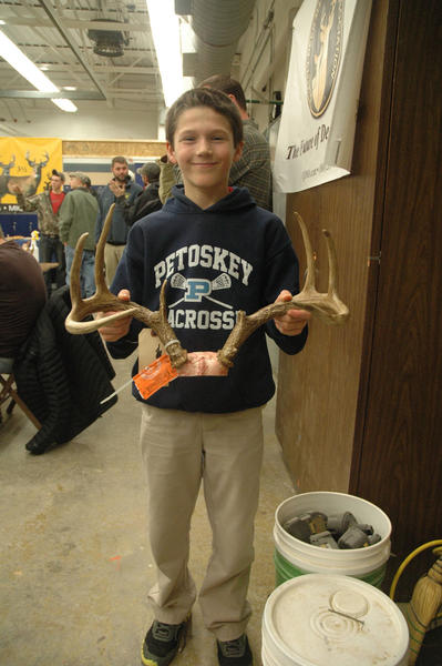 Forest Walker, 11, of Petoskey, displays the rack from his first buck, taken this firearm season, recently at a deer scoring and aging night that took place at Petoskey High School.