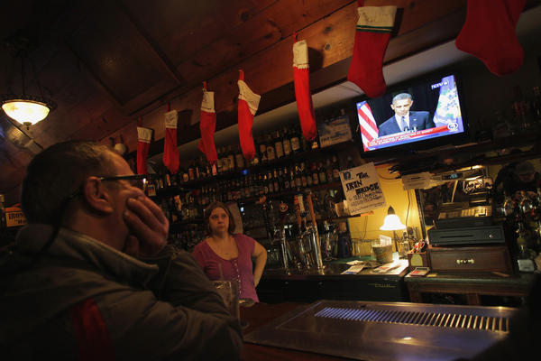 A patron and a bartender watch President Barack Obama speak on a television at Church Hill restaurant in Newtown, Conn. Obama, speaking at a vigil at Newtown High School on Sunday, consoled the Connecticut town shattered by the massacre of 20 young schoolchildren, lauding residents' courage in the face of tragedy and saying the United States was not doing enough to protect its children.