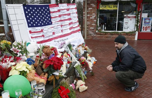 Mark Sorrentino, of Naugatuck, Conn., pays respects Monday near a U.S. flag carrying the names of victims on a makeshift memorial in the Sandy Hook village of Newtown.