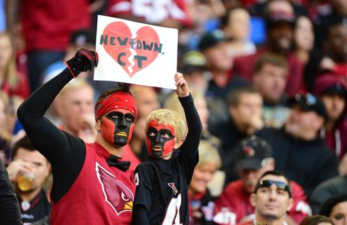 Arizona Cardinals fans hold a sign in remembrance of the victims of the Sandy Hook Elementary shooting.